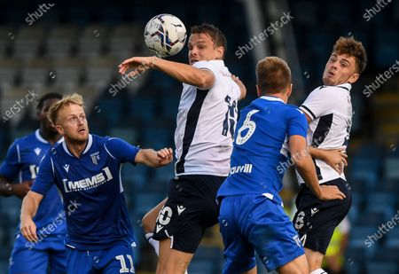 Matt Smith of Millwall and Ben Thompson of Millwall battle with Ben Reeves of Gillingham and Jack Tucker of Gillingham