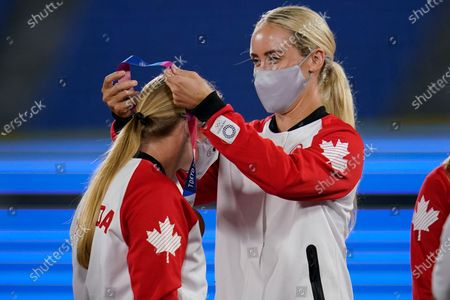 Stock Image of Canada's Jennifer Gilbert, right, places a bronze medal around the neck of teammate Emma Entzminger, left, during the medal ceremony for softball at the 2020 Summer Olympics, in Yokohama, Japan