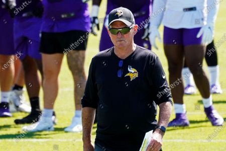 Minnesota Vikings head coach Mike Zimmer walks through the field during NFL football practice in Eagan, Minn. The Vikings and assistant coach Rick Dennison have found a solution for him to remain with the club despite his unvaccinated status. The 63-year-old Dennison will take a role as senior offensive advisor. He'll do all of his collaboration with the staff virtually