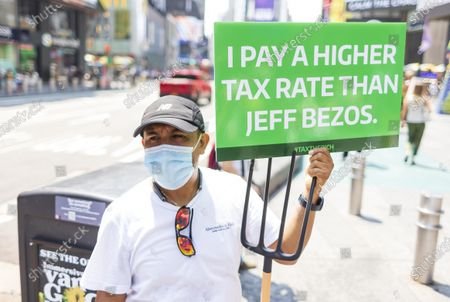 A man takes part in a small rally calling for a higher tax rate on the wealthiest Americans which was organized partially in response to recent, privately funded trips into space by billionaires Jeff Bezos and Richard Branson in Times Square in New York, New York, USA, 27 July 2021. Following short trips into low orbit space by Bezos and Branson, some have criticized the cost of the trips and are calling for higher taxes on the wealth.