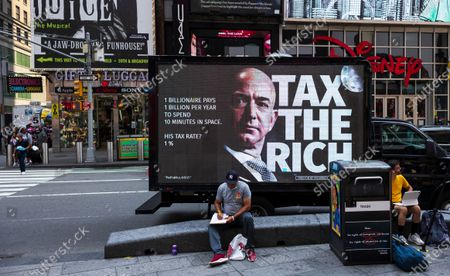 Stock Image of A mobile billboard on a truck is parked near a small rally calling for a higher tax rate on the wealthiest Americans which was organized partially in response to recent, privately funded trips into space by billionaires Jeff Bezos and Richard Branson in Times Square in New York, New York, USA, 27 July 2021. Following short trips into low orbit space by Bezos and Branson, some have criticized the cost of the trips and are calling for higher taxes on the wealth.