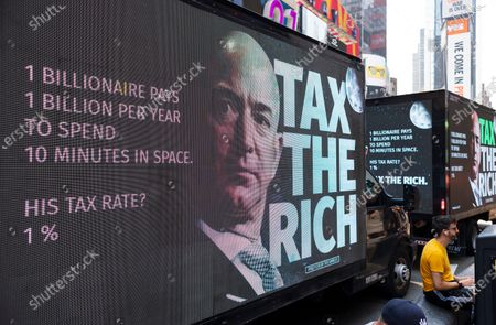 Mobile billboards on trucks parked near a small rally calling for a higher tax rate on the wealthiest Americans which was organized partially in response to recent, privately funded trips into space by billionaires Jeff Bezos and Richard Branson in Times Square in New York, New York, USA, 27 July 2021. Following short trips into low orbit space by Bezos and Branson, some have criticized the cost of the trips and are calling for higher taxes on the wealth.