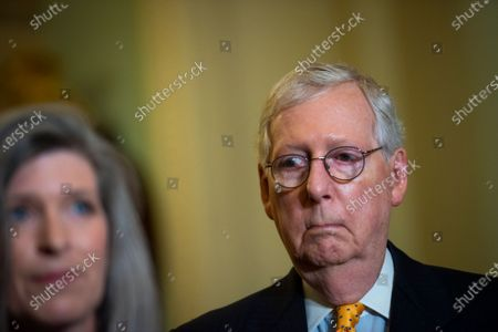 Stock Image of United States Senate Minority Leader Mitch McConnell (Republican of Kentucky) listens while United States Senator Joni Ernst (Republican of Iowa) offers remarks during a press conference following the Senate Republican's policy luncheon at the US Capitol in Washington, DC,.