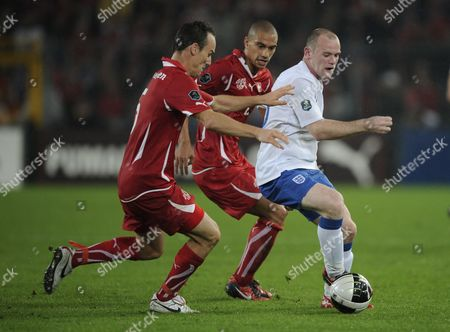 Wayne Rooney of England is covered by Steven von Bergen (l) and Gokhan Inler (m) of Switzerland