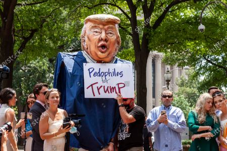 """A protester wears a giant Trump costume, while another holds a """"Pedophiles for Trump"""" sign at a press conference held by Representatives Matt Gaetz (R-FL), Majorie Taylor Greene (R-GA), Paul Gosar (R-AZ), and Louie Gohmert :R-TX).  The sign is a reference to accusations against Gaetz of sex with underage girls.  5 of the 6 Representatives fled their own press conference after protesters arrived.  The press conference took place while police officers testified to the House Select Committee about the January 6 insurrection."""