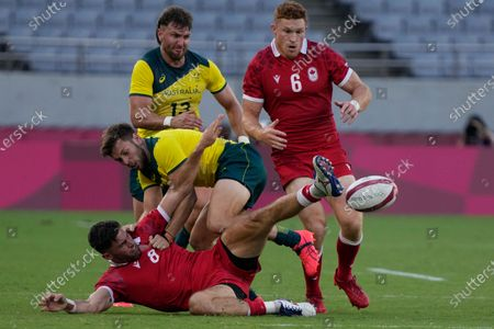 Stock Image of Canada's Justin Douglas, bottom, makes the pass under pressure from Australia's Josh Turner, in their men's rugby sevens 7-8 placing match at the 2020 Summer Olympics, in Tokyo, Japan