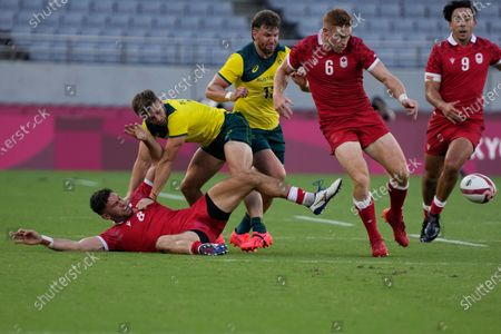 Canada's Justin Douglas, bottom, tussles with Australia's Josh Turner, as Canada's Connor Braid, second right, Canada's Nathan Hirayama, and Australia's Lewis Holland run in their men's rugby sevens 7-8 placing match at the 2020 Summer Olympics, in Tokyo, Japan