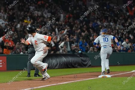 San Francisco Giants' Buster Posey, left, runs home to score as Los Angeles Dodgers third baseman Justin Turner (10) looks for the ball after a throwing error by first baseman Cody Bellinger during the eighth inning of a baseball game in San Francisco