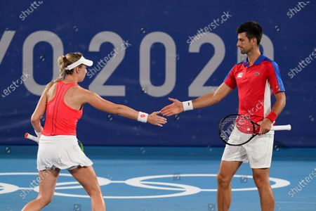 Nina Sojanovic, left, and Novak Djokovic, of Serbia, high five during a first round mixed doubles tennis match against Luisa Stefani and Marcelo Melo, of Brazil, at the 2020 Summer Olympics, in Tokyo, Japan