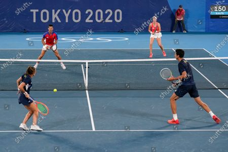 Novak Djokovic, top left, and Nina Sojanovic, of Serbia, prepare to return to Luisa Stefani, bottom left, and Marcelo Melo, of Brazil, during a first round mixed doubles tennis match at the 2020 Summer Olympics, in Tokyo, Japan