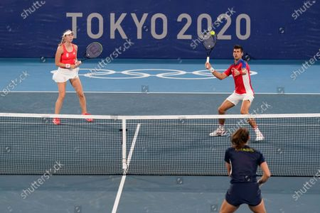 Novak Djokovic, right, and Nina Sojanovic, of Serbia, return to Luisa Stefani, bottom right, and Marcelo Melo, of Brazil, during a first round mixed doubles tennis match at the 2020 Summer Olympics, in Tokyo, Japan