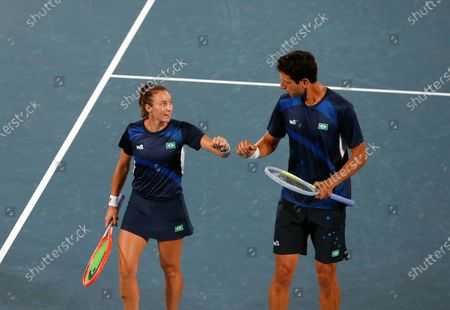 Stefani Luisa (L) and Marcelo Melo (R) of Brazil celebrate a point against Nina Stojanovic and Novak Djokovic of Serbia during their Mixed Doubles First Round Tennis match of the Tokyo 2020 Olympic Games at the Ariake Coliseum in Tokyo, Japan, 28 July 2021.