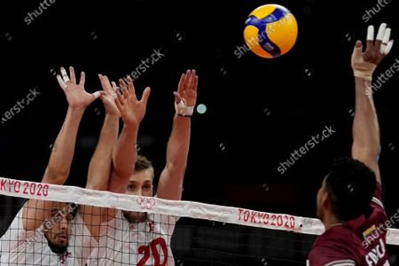 Poland's Fabian Drzyzga, from left, and Poland's Mateusz Bieniek block the ball hit by Venezuela's Jose Manuel Carrasco Angulo during the men's volleyball preliminary round pool A match between Poland and Venezuela at the 2020 Summer Olympics, in Tokyo, Japan