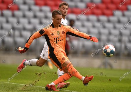 Munich's goalkeeper Ron-Thorben Hoffmann (front) in action against Moenchengladbach's Mika Schroers (back) during the Audi Football Summit pre-season friendly test soccer match between Bayern Munich and Borussia Moenchengladbach in Munich, Germany, 28 July 2021.