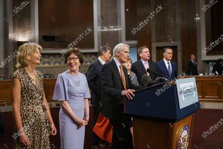 The bipartisan group of Senate negotiators speak to reporters just after a vote to start work on a nearly $1 trillion bipartisan infrastructure package, at the Capitol in Washington, .From left are Sen. Lisa Murkowski, R-Alaska, Sen. Susan Collins, R-Maine, Sen. Joe Manchin, D-W.Va., Sen. Rob Portman, R-Ohio, Sen. Jeanne Shaheen, D-N.H., Sen. Mark Warner, D-Va., and Sen. Mitt Romney, R-Utah
