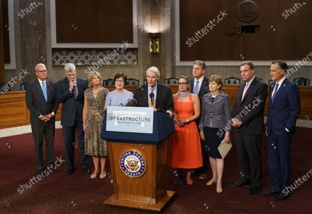 The bipartisan group of Senate negotiators speak to reporters just after a vote to start work on a nearly $1 trillion bipartisan infrastructure package, at the Capitol in Washington, . From left are Rep. Kevin Cramer, R-N.D., Sen. Bill Cassidy, R-La., Sen. Lisa Murkowski, R-Alaska, Sen. Susan Collins, R-Maine, Sen. Rob Portman, R-Ohio, Sen. Kyrsten Sinema, D-Ariz., Sen. Joe Manchin, D-W.Va., Sen. Jeanne Shaheen, D-N.H., Sen. Mark Warner, D-Va., and Sen. Mitt Romney, R-Utah