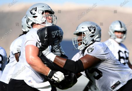 Las Vegas Raiders center Jimmy Morrissey, left, and offensive tackle Brandon Parker perform drills during an NFL football practice, in Henderson, Nev