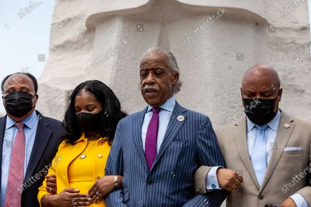 Rev. Reverend Al Sharpton leads members of the Texas Black Legislative Caucus, Martin Luther King III, and Arndrea King in prayer at the end of a press conference on voting rights at the Martin Luther King Jr. Memorial. Caucus members are in Washington, DC, while breaking quorum to prevent passage of a bill regricting voting rights in the Texas legislature. Left to right: Martin Luther King III, Arndrea King, Rev. Reverend Al Sharpton, Rep. Carl Sherman.