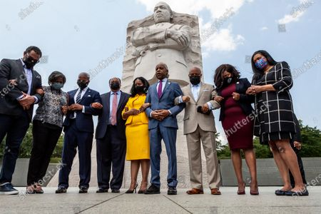 Stock Image of Rev. Reverend Al Sharpton leads members of the Texas Black Legislative Caucus, Martin Luther King III, and Arndrea King in prayer at the end of a press conference on voting rights at the Martin Luther King Jr. Memorial. Caucus members are in Washington, DC, while breaking quorum to prevent passage of a bill regricting voting rights in the Texas legislature. Left to right: Rep. Jarvis Johnson, Rep. Rhetta Bowers, Martin Luther King III, Arndrea King, Rev. Reverend Al Sharpton, Rep. Carl Sherman, Rep. Jasmine Crockett, and Rep. Shawn Thierry.