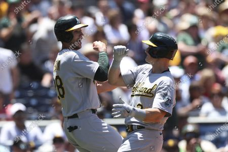 Stock Picture of Oakland Athletics' Matt Chapman, right, celebrates with Matt Olson, left, after hitting a home run against the San Diego Padres in the first inning a baseball game, in San Diego