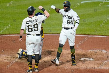 Pittsburgh Pirates' Rodolfo Castro, right, celebrates with John Nogowski (69) after hitting a two-run home run off Milwaukee Brewers relief pitcher Josh Hader during the ninth inning of a baseball game in Pittsburgh, . The Brewers won 7-3