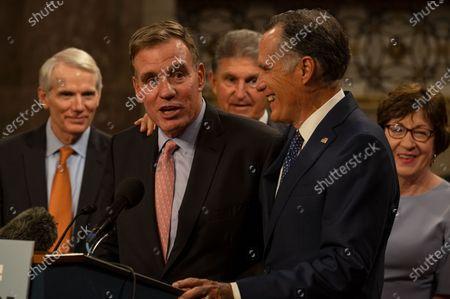 U.S. Senator Mitt Romney (R-UT) puts his arm around U.S. Senator Mark Warner (D-VA) as a group of bipartisan senators hold a press conference after advancing infrastructure legislation through the Senate in Washington, DC, on July 28, 2021