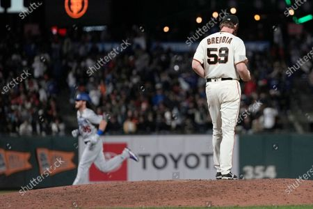 San Francisco Giants relief pitcher John Brebbia (59) stands on the mound as Los Angeles Dodgers' Cody Bellinger runs the bases after hitting a solo home run during the eighth inning of a baseball game, in San Francisco