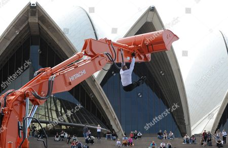 Stock Image of Performer Philippe Priasso dances with a digger