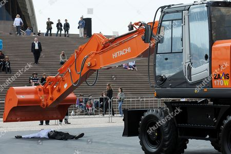 Stock Photo of Performer Philippe Priasso dances with a digger