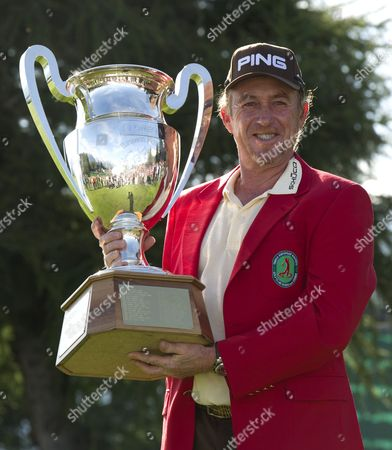 Miguel Angle Jimenez holds the Omega Masters Trophy and wears the Red Jacket after winning the tournament