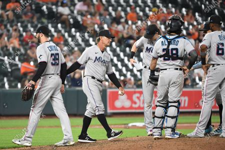 Miami Marlins manager Don Mattingly center, removes relief pitcher John Curtiss (39) from the game during the eighth inning of a baseball game against the Baltimore Orioles, in Baltimore
