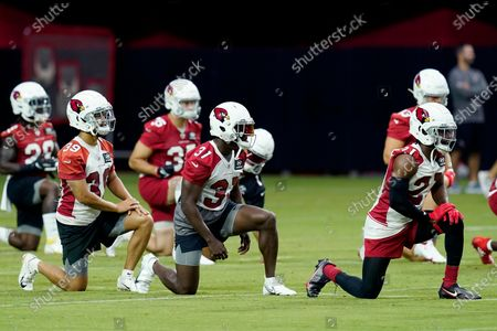 Arizona Cardinals cornerback Jace Whittaker (39), Cardinals defensive back Chris Banjo (31) and Cardinals cornerback Malcolm Butler, right, stretch out with teammates during NFL football training camp practice, in Glendale, Ariz