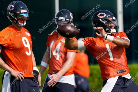 Chicago Bears quarterbacks Nick Foles, left, and Andy Dalton watch as quarterback Justin Fields, right, looks to pass during NFL football practice in Lake Forest, Ill