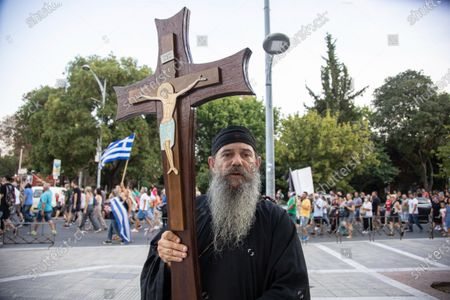 A priest is carrying a cross with Jesus during the demonstration. Hundreds of people, less than the big previous rally, are seen at the Demonstration Against The Mandatory Vaccine that was held in Thessaloniki in Greece on Wednesday July 28, 2021. One week after the massive protest against the mandatory vaccination the anti-vaxx campaign continues with a big group protesting in the streets of the city of Thessaloniki. The protest was organized via social media by anti-vaccination believers. According to the group more than 5000 people participated, while the police estimated unofficially slightly around 2.000 people participating in the demonstration. As the Greek government is passing a legislation with mandatory vaccination to specific job sectors like medical healthcare workers etc people are protesting against it. Protesters marched in the center of Thessaloniki where car traffic was stopped for a couple of hours. Nationalists and religious groups supported the demo spelling many slogans against the Prime Minister Mitsotakis and Journalists. The protesting group passed in front of ERT, the public television broadcaster, where participants shouted against them and some voices were saying to enter and occupy the building. The demonstration ended at the statue of Alexander the Great while it began from the White Tower, symbol of the city. Riot police monitored the event carefully with a distance to avoid violent incidents from radicals. A small group of hospital workers participated not against the vaccination, but against the mandatory action. Greece is having a surge in COVID-19 Coronavirus cases as the pandemic rises again due to the Delta Mutation variant and the peaking in the vaccination program, applying some local lockdowns to areas like the Greek Islands. Thessaloniki, Greece on July 28, 2021