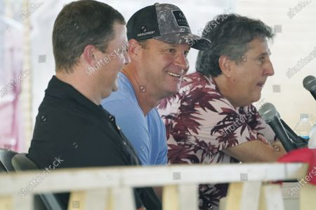 """Mississippi NCAA Division 1 football coach, Lane Kiffin of Mississippi, center, laughs at a question during a special """"Football at the Fair"""" program at the Neshoba County Fair along fellow coaches Will Hall of Southern Mississippi, left, and Mike Leach of Mississippi State, in Philadelphia, Miss., . The fair, also known as Mississippi's Giant House Party, is an annual event of agricultural, political, and social entertainment at what might be the country's largest campground fair"""
