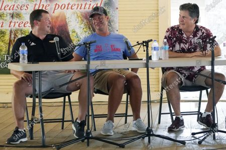 """All three Mississippi NCAA Division 1 football coaches, from left, Will Hall of Southern Mississippi, Lane Kiffin of Mississippi, and Mike Leach of Mississippi State, joke with each other during a special """"Football at the Fair"""" program at the Neshoba County Fair in Philadelphia, Miss., . The fair, also known as Mississippi's Giant House Party, is an annual event of agricultural, political, and social entertainment at what might be the country's largest campground fair"""