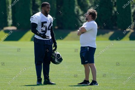 Seattle Seahawks middle linebacker Bobby Wagner talks with general manager John Schneider, right, following NFL football practice, in Renton, Wash