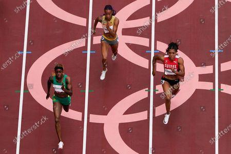 Elaine Thompson-Herah, of Jamaica, Tatjana Pinto, of Germany, and nd Mujinga Kambundji, of Switzerland, compete during the first round of the women's 100-meter the 2020 Summer Olympics, in Tokyo