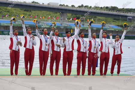 Wang Zifeng, Wang Yuwei, Xu Fei, Miao Tian, Zhang Min, Ju Rui, Li Jingjing, Guo Linlin, and Zhang Dechang of China celebrate winning the bronze medal for the women's rowing eight final at the 2020 Summer Olympics, in Tokyo, Japan