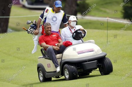 Jhonattan Vegas of Venezuela (L) rides off the eighteenth hole after play was suspended due to lightning in the area during the second round of the Golf events of the Tokyo 2020 Olympic Games at the Kasumigaseki Country Club in Kawagoe, Japan, 30 July 2021.