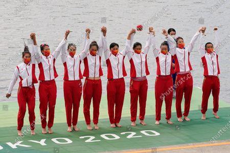 Stock Image of Wang Zifeng, Wang Yuwei, Xu Fei, Miao Tian, Zhang Min, Ju Rui, Li Jingjing, Guo Linlin, and Zhang Dechang of China celebrate winning the bronze medal in the women's rowing eight final at the 2020 Summer Olympics, in Tokyo, Japan
