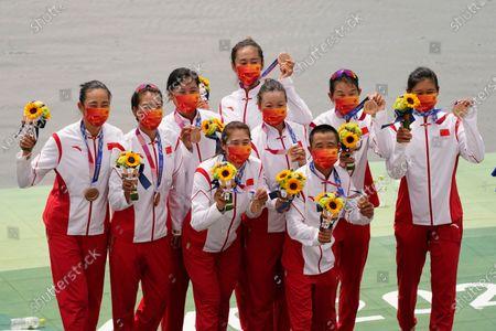 Wang Zifeng, Wang Yuwei, Xu Fei, Miao Tian, Zhang Min, Ju Rui, Li Jingjing, Guo Linlin, and Zhang Dechang of China celebrate winning the bronze medal in the women's rowing eight final at the 2020 Summer Olympics, in Tokyo, Japan