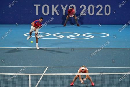 The Serbian mixed doubles team of Novak Djokovic, left, and Nina Stojanovic play during the semifinals of the tennis competition at the 2020 Summer Olympics, in Tokyo, Japan