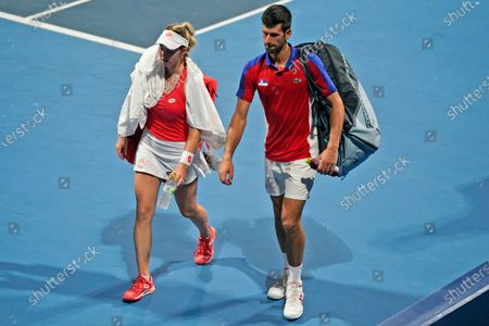 The Serbian mixed doubles team of Novak Djokovic, right, and Nina Stojanovic leave the court after being defeated by a team from the Russian Olympic Committee during the semifinals of the tennis competition at the 2020 Summer Olympics, in Tokyo, Japan