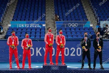 Silver medalists Marin Cilic and Ivan Dodig, from left, of Croatia, gold medalists Mate Pavic, and Nikola Mektic, of Croatia, and bronze medalists Michael Venus and Marcus Daniell, of New Zealand, stand for the Croatian national anthem during a ceremony for the men's doubles tennis competition at the 2020 Summer Olympics, in Tokyo, Japan