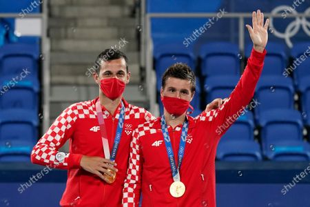 Mate Pavic, left, and Nikola Mektic, of Croatia, pose with their gold medals during a medals ceremony for the men's doubles tennis competition at the 2020 Summer Olympics, in Tokyo, Japan