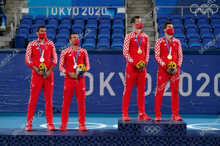 Silver medalists Marin Cilic, left, and Ivan Dodig, of Croatia, and gold medalists Mate Pavic, second from right, and Nikola Mektic, of Croatia, stand for the Croatian national anthem during a ceremony for the men's doubles tennis competition at the 2020 Summer Olympics, in Tokyo, Japan
