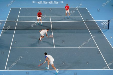 Marin Cilic and Ivan Dodig, of Croatia, return to Nikola Mektic and Mate Pavic, of Croatia, during the final round of the men's doubles tennis competition at the 2020 Summer Olympics, in Tokyo, Japan