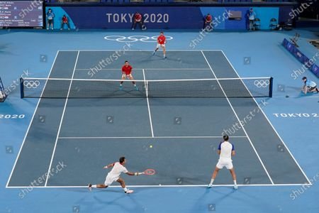 Ivan Dodig and Marin Cilic, of Croatia, return to Nikola Mektic and Mate Pavic, of Croatia, during the final round of the men's doubles tennis competition at the 2020 Summer Olympics, in Tokyo, Japan