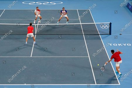 Mate Pavic, bottom right, and Nikola Mektic, of Croatia, return to Ivan Dodig, top left, Marin Cilic, of Croatia, during the final round of the men's doubles tennis competition at the 2020 Summer Olympics, in Tokyo, Japan